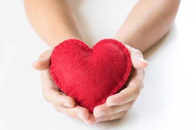 Corazón de fieltro rojo en manos de niños sobre blanco.