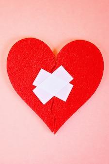 Un corazón de fieltro rojo roto en dos mitades, pegadas con yeso sobre un fondo rosa.