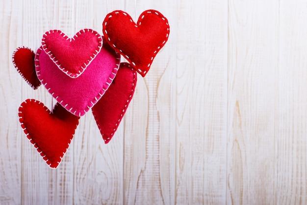 Corazón de fieltro rojo sobre una cuerda, sobre fondo blanco de madera