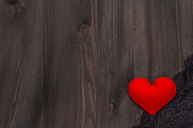 Corazón de fieltro rojo y tela de encaje sobre mesa de madera
