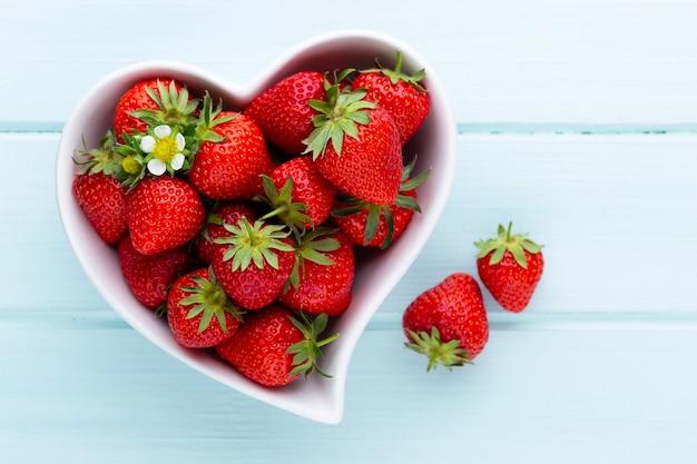 Corazón de fresa fresas frescas en placa sobre mesa de madera blanca vista superior espacio de copia