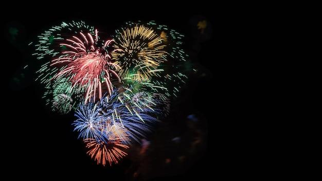 Corazón de fuegos artificiales multicolores en el cielo negro, espacio de copia