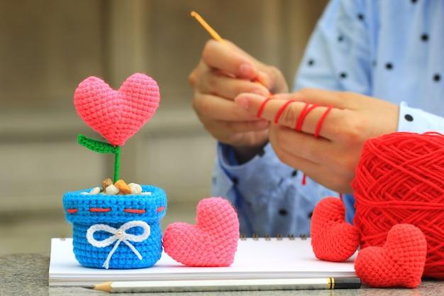 Corazón de ganchillo hecho a mano y mujer con su ganchillo, día de san valentín