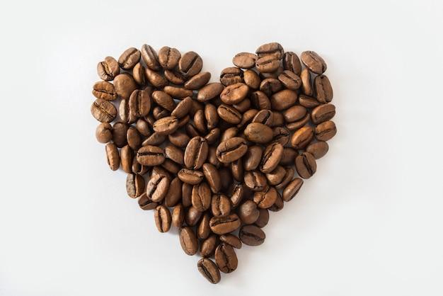 Corazón de granos de café sobre una superficie blanca