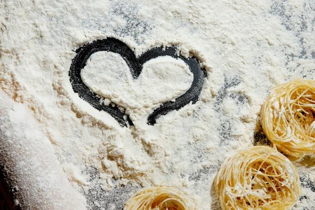 Corazón de harina y rodillo sobre fondo negro. vista superior, copie el espacio.