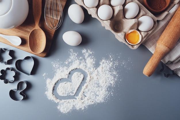 Corazón de harina y utensilios de cocina. concepto de san valentín. hacer galletas caseras para el día de san valentín, vista superior, endecha plana. ingredientes para hornear sobre un fondo gris.