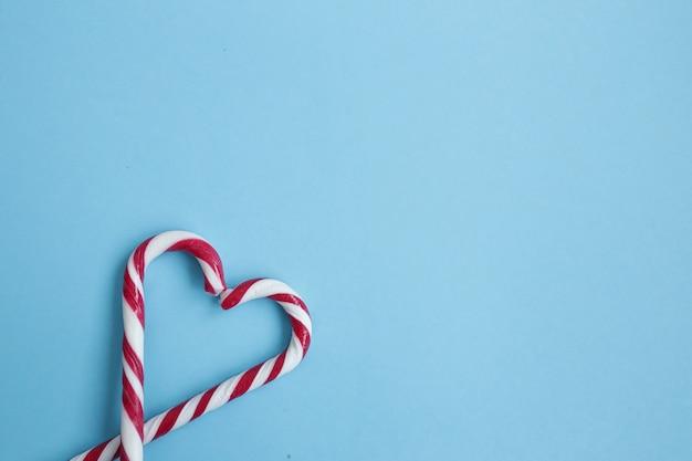 Corazón hecho de bastones de caramelo aislado sobre fondo azul. bastones de caramelo dispuestos en forma de corazón. concepto de amor copyspace