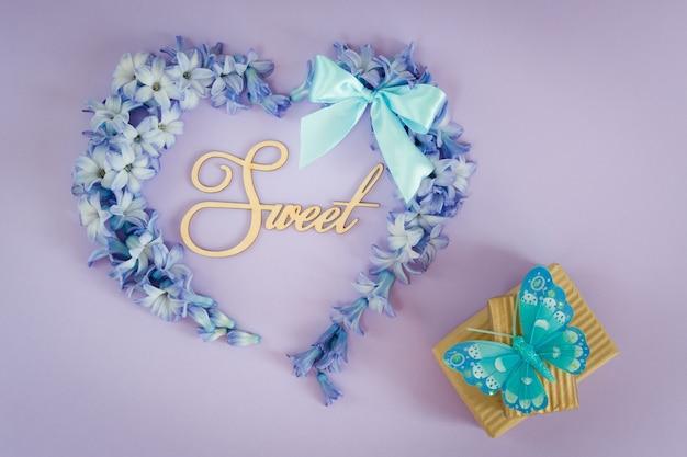 Corazón hecho de flores de jacinto con arco de menta y cajas de regalo con mariposa sobre fondo púrpura
