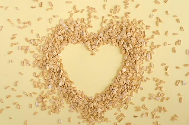 Corazón hecho de granos de avena sobre fondo amarillo pastel