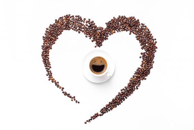 Corazón hecho de granos de café y café molido sobre una superficie blanca. en el centro hay una taza, en una taza de espuma de café una cara sonriente y feliz. concepto de bebida vigorizante