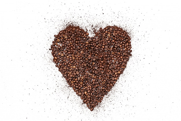 Corazón hecho de granos de café tostado y café molido sobre una superficie blanca