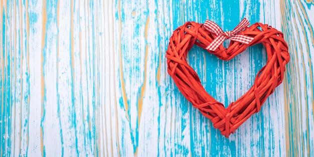 Corazón hecho a mano rojo sobre fondo de madera azul, plantilla con espacio de copia. tarjeta de felicitación romántica en estilo vintage y diseño lacónico. san valentín - vacaciones.