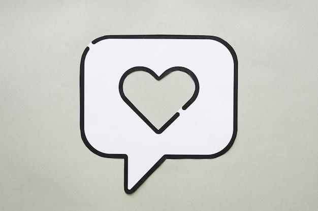 Corazón en el icono de discurso de burbuja en la mesa
