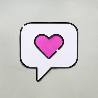 Corazón en el icono de voz de burbuja en la mesa gris