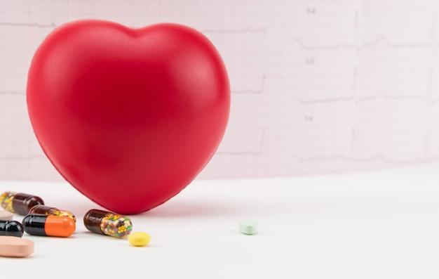 Corazón de juguete con pastillas sobre fondo de electrocardiograma cuidado de cardiología del corazón