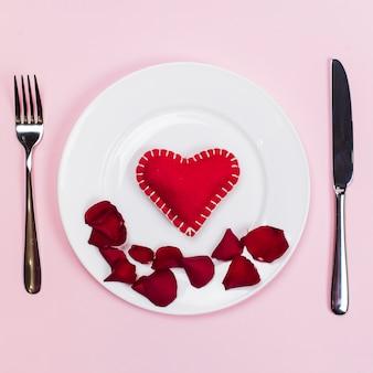 Corazón de juguete con pétalos de flores en un plato