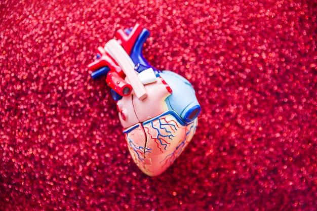 Corazón de juguete recostado sobre purpurina.