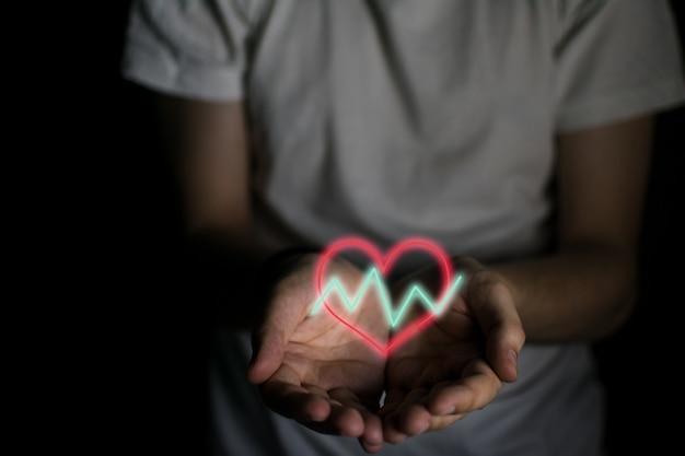 Corazón con líneas fluctuantes en las manos de un hombre.