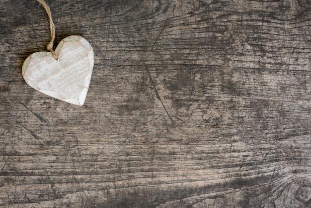 Corazón de madera blanca en la mesa rústica