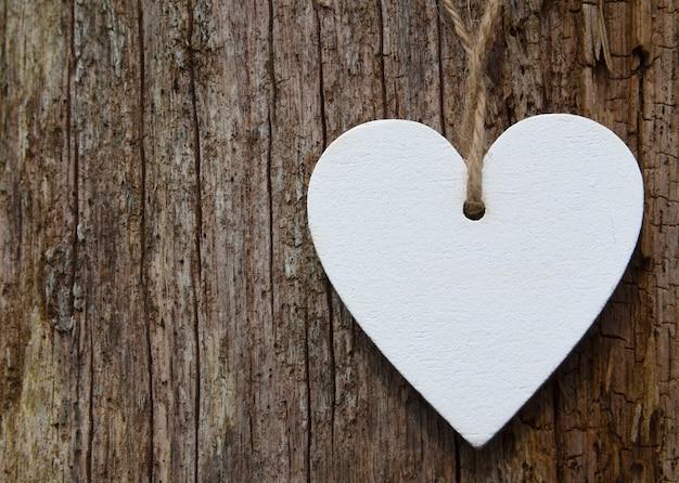 Corazón de madera blanco decorativo sobre fondo de madera vieja. concepto de san valentín o del amor. foco selectivo.