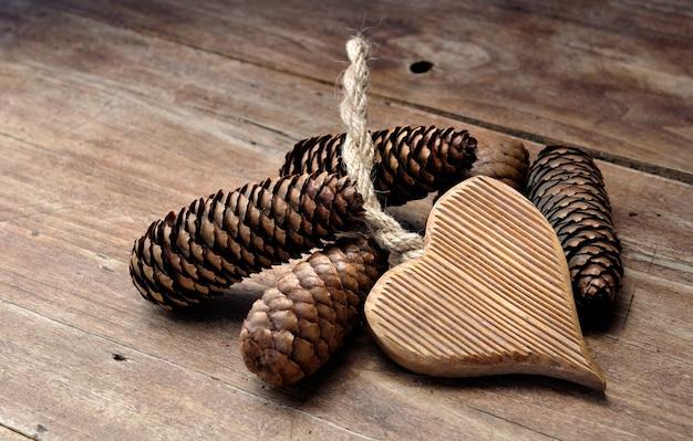 Corazón de madera y conos de pino sobre una plancha
