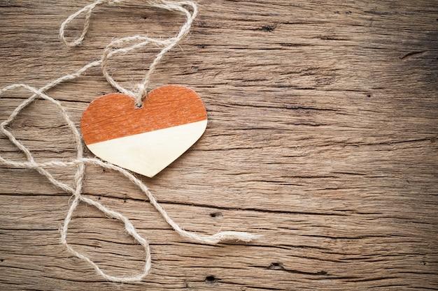 Corazón de madera con cuerda en madera vieja