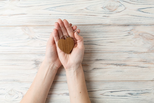 Corazón de madera en la palma de la mujer de cerca.