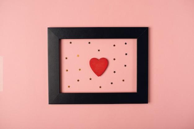 Corazón de madera rojo y estrellitas doradas en el marco de fotos negro. concepto de san valentín. vista plana endecha, superior.