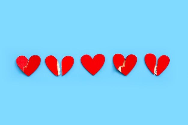 Corazón de madera roto sobre fondo azul.
