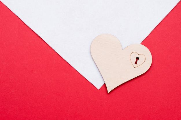 Corazón de madera sobre superficie blanca y roja