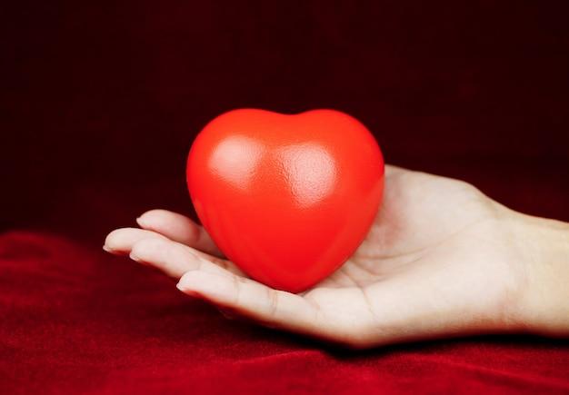 Corazón en la mano para la filantropía mujer sosteniendo un corazón rojo en las manos para el día de san valentín o donar ayuda