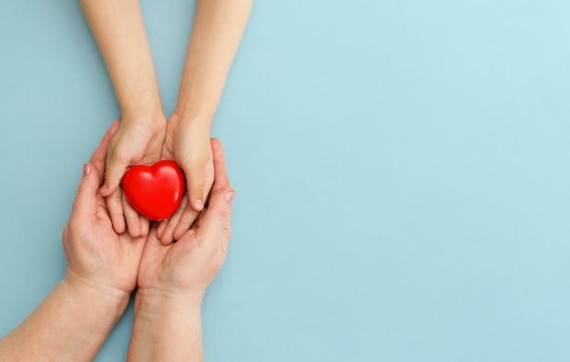 Corazón en manos de la hija y la madre sobre un fondo azul.