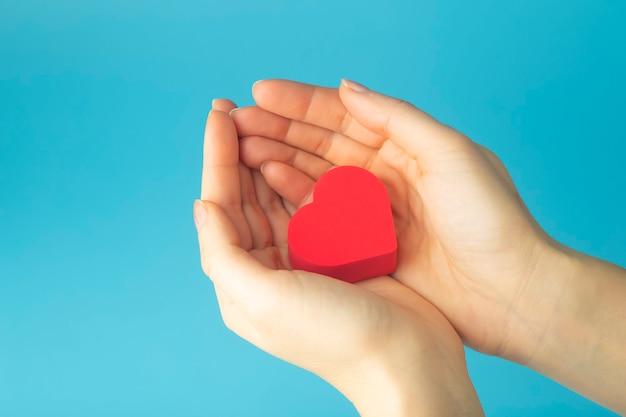 Corazón en manos de una mujer sobre un fondo de color. fondo para san valentín (14 de febrero) y amor.