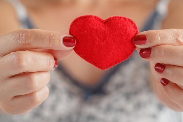 Corazón en manos de mujer
