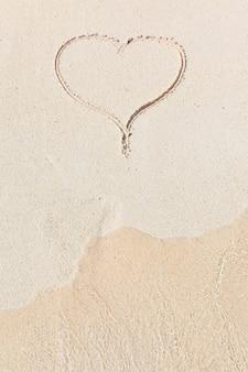 Corazón manuscrito en arena con ola acercándose en la playa