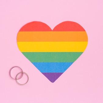 Corazón multicolor de lgbt y anillos de boda.