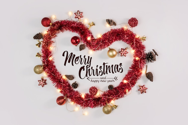 Corazón de navidad y adornos sobre superficie blanca