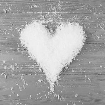 Corazón de nieve decorativa en mesa de madera.