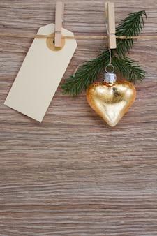 Corazón de oro de navidad y ramita de hoja perenne con etiqueta vacía colgando de clotheline