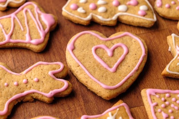 Corazón de pan de jengibre para el día de san valentín en la mesa de madera con otras galletas caseras.