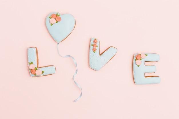 Corazón de pan de jengibre, galletas en forma de carta de amor con glaseado sobre fondo rosa pastel.