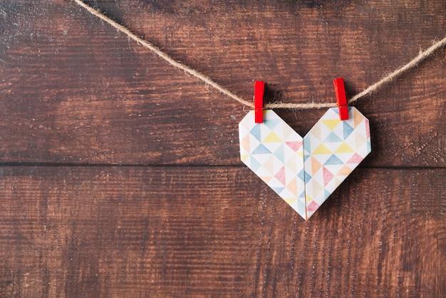 Corazón de papel con alfileres enganchados en hilo.
