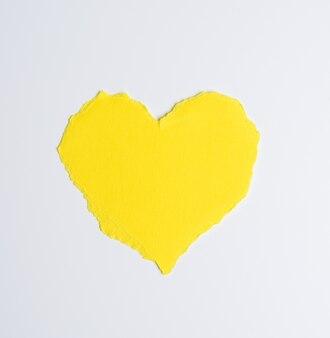 Corazón de papel amarillo sobre fondo blanco, cerrar