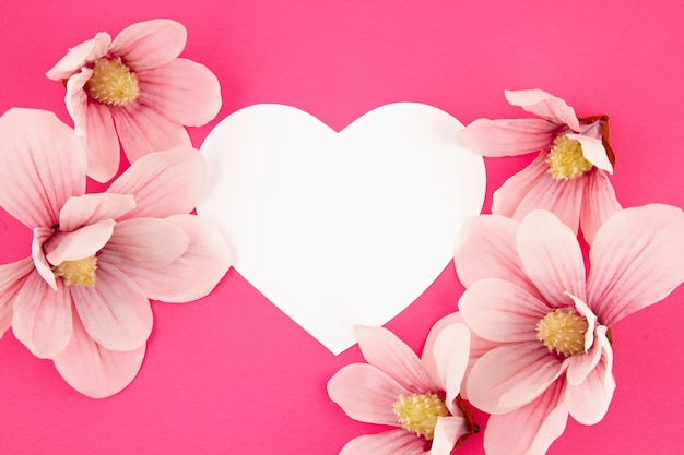 Corazón de papel blanco y flores de magnolia sobre fondo rosa.