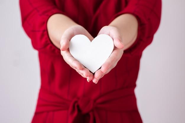 Corazón de papel blanco está siendo archivado por mano de mujer.