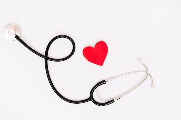 Corazón de papel cerca del estetoscopio