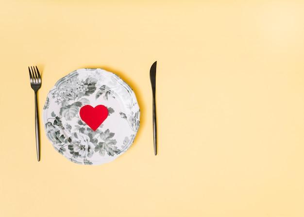 Corazón de papel decorativo en plato hermoso entre cubiertos.
