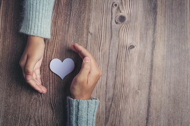 Corazón de papel y las manos de la pareja en la mesa de madera