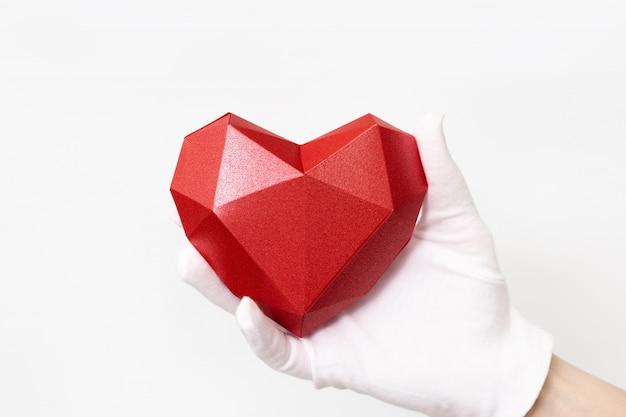 Corazón de papel poligonal rojo en la mano con guante de tela blanca