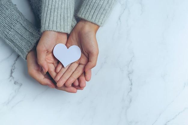 Corazón de papel puesto en manos de la pareja sobre la mesa de mármol